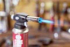 Gaspatronen-Gewehrfeuerzeug Nahaufnahmedüse des Brenners mit Jet der blauen Flamme Werkstatthintergrund, Versengung des Holzes lizenzfreie stockfotografie
