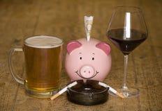 Gaspillage d'argent fumant et buvant photographie stock libre de droits