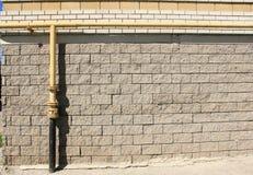 Gasrohr auf einer Backsteinmauer Stockbilder
