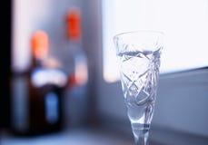 Gass av alkohol på fönsterskrivbordbakgrund royaltyfria bilder
