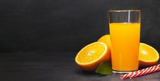 Gass av ny orange fruktsaft med nya frukter på den mörka tabellen royaltyfria bilder