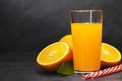 Gass av ny orange fruktsaft med nya frukter på den mörka tabellen royaltyfri fotografi