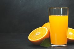 Gass av ny orange fruktsaft med nya frukter p? den m?rka tabellen arkivbild