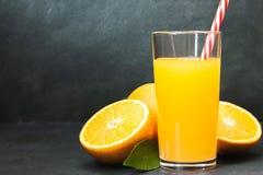 Gass av ny orange fruktsaft med nya frukter p? den m?rka tabellen royaltyfria bilder