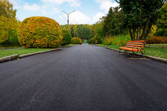 Gasse in einem allgemeinen Park mit Bänke und Laternen morgens Lizenzfreie Stockbilder