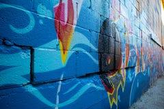 Gassenweise mit Graffiti auf einer Backsteinmauer stockfotos