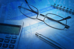Gasses pen and calculator on financial chart and graph Royalty Free Stock Photo