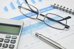 Gasses pen and calculator on financial chart and graph. Accounting background Stock Photography