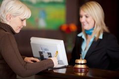 Gast, der herauf einen Formular am Hotelzähler füllt lizenzfreies stockfoto