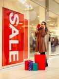 Gastar dinero de la mujer para hacer compras en la alameda de compras Foto de archivo libre de regalías