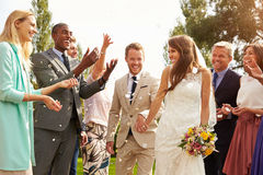 Gasten die Confettien over Bruid en Bruidegom At Wedding werpen Royalty-vrije Stock Afbeeldingen