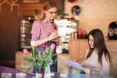 Gastfreundliche Kellnerin mit Briefpapier und Bleistift bereit, Ihre Bestellung entgegenzunehmen stockfoto