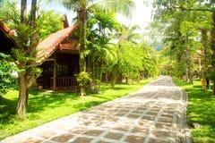 Gasthuizen onder palmen met weg thailand Stock Fotografie