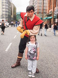 Gaston and a young girl at Disneyland Paris. Gaston from Beauty and the beast leans on the head of a young girl at Disneyland Paris Royalty Free Stock Images