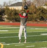 Gastos indirectos de la bola de medicina del atleta de la High School que lanzan secundaria Fotos de archivo