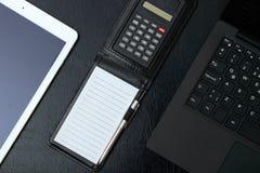 Gastos indirectos de la tabla de la oficina con el cuaderno, teclado de ordenador, tabla fotos de archivo