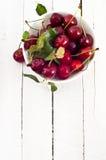 Gastos indirectos del cuenco de cerezas rojas en el plato blanco Imagen de archivo