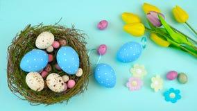 Gastos indirectos felices de Pascua con los huevos y las decoraciones de Pascua en un fondo de madera