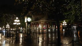 Gastown Night Steamclock Vancouver. Reflections on the wet street during a rainy night in Vancouver`s touristy Gastown district. British Columbia, Canada stock video footage