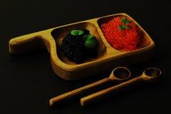 gastrónomo Caviar negro y rojo apetitoso en la bandeja de madera con las cucharas de madera en fondo oscuro fotografía de archivo