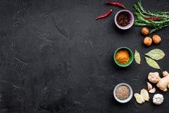 Gastronomi som är kulinarisk Hemligheter av smaklig disk Krydda och kryddor Rosmarin ingefära, chilipeppar på svart bakgrund Arkivfoto