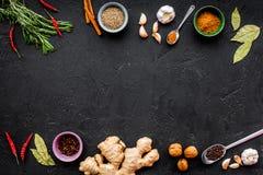 Gastronomi som är kulinarisk Hemligheter av smaklig disk Krydda och kryddor Rosmarin ingefära, chilipeppar på svart bakgrund Fotografering för Bildbyråer
