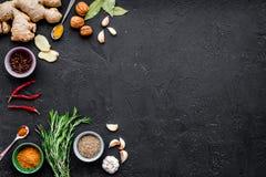 Gastronomi som är kulinarisk Hemligheter av smaklig disk Krydda och kryddor Rosmarin ingefära, chilipeppar på svart bakgrund Royaltyfri Fotografi