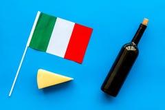 Gastronomisch toerisme Italiaanse voedselsymbolen Italiaanse vlag, kaasparmezaanse kaas en fles rode wijn op blauwe bovenkant als stock afbeelding