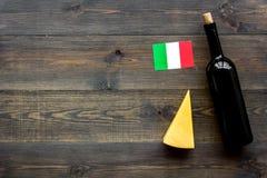 Gastronomisch toerisme Italiaanse voedselsymbolen Italiaanse vlag, kaasparmezaanse kaas en fles rode wijn op donkere houten stock afbeelding