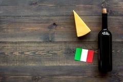 Gastronomisch toerisme Italiaanse voedselsymbolen Italiaanse vlag, kaasparmezaanse kaas en fles rode wijn op donkere houten stock fotografie