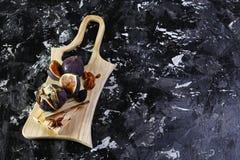 Gastronomisch voorgerecht van fig. met dorblyukaas, okkernoten en honing op een houten raad een donkere achtergrond, traditioneel royalty-vrije stock afbeeldingen
