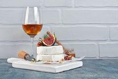Gastronomisch voorgerecht van witte Briekaas of camembert met verse fig., noten en glas wijn voor het proeven stock foto
