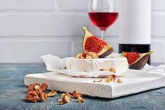 Gastronomisch voorgerecht van witte Briekaas of camembert met verse fig., noten en rode wijn op houten scherpe raad royalty-vrije stock fotografie