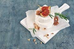 Gastronomisch voorgerecht van witte Briekaas of camembert met verse fig., noten en rozemarijnkruid op houten raad stock afbeelding