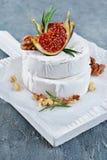 Gastronomisch voorgerecht van witte Briekaas of camembert met verse fig., noten en rozemarijnkruid op houten raad stock foto