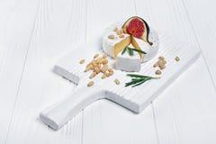 Gastronomisch voorgerecht van witte Briekaas of camembert met verse fig., pijnboomnoten en rozemarijnkruid royalty-vrije stock foto