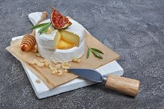 Gastronomisch voorgerecht van witte Briekaas of camembert met verse fig., pijnboomnoten, honing en rozemarijnkruid op houten raad stock foto's