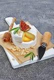 Gastronomisch voorgerecht van witte Briekaas of camembert met verse fig., pijnboomnoten, honing en rozemarijnkruid op houten raad stock afbeelding