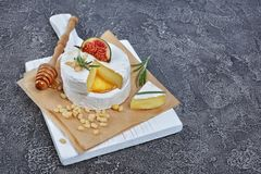 Gastronomisch voorgerecht van witte Briekaas of camembert met verse fig., pijnboomnoten, honing en rozemarijnkruid op houten raad stock fotografie