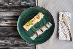 gastronomisch zoet dessert met amandelen en munt op plaat en vork met mes op servet royalty-vrije stock afbeelding