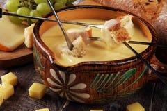 Gastronomisch Zwitsers fonduediner op een de winteravond met geassorteerde kazen op een raad naast een verwarmde pot van kaasfond stock foto's