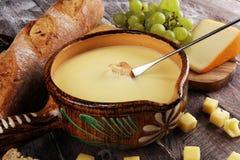 Gastronomisch Zwitsers fonduediner op een de winteravond met geassorteerde kazen op een raad naast een verwarmde pot van kaasfond stock afbeeldingen