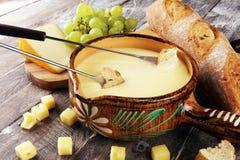 Gastronomisch Zwitsers fonduediner op een de winteravond met geassorteerde kazen op een raad naast een verwarmde pot van kaasfond royalty-vrije stock afbeeldingen