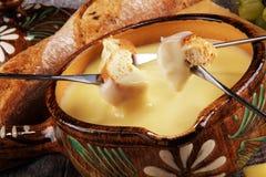 Gastronomisch Zwitsers fonduediner op een de winteravond met geassorteerde kazen op een raad naast een verwarmde pot van kaasfond royalty-vrije stock afbeelding