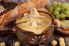 Gastronomisch Zwitsers fonduediner op een de winteravond met geassorteerde kazen op een raad naast een verwarmde pot van kaasfond stock afbeelding