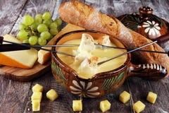 Gastronomisch Zwitsers fonduediner op een de winteravond met geassorteerde kazen op een raad naast een verwarmde pot van kaasfond royalty-vrije stock fotografie