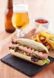 Gastronomische hotdog op leiraad Royalty-vrije Stock Afbeeldingen