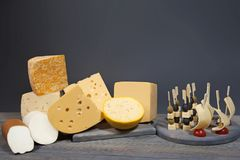 Gastronomische Zusammensetzung von den verschiedenen Arten des Käses und der Aufsteckspindeln mit Aperitifs auf Holztisch Lizenzfreie Stockbilder