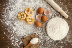 Gastronomy cooking process. Cooking some delicious thing with eggs, flour and fettuccine with kitchenware help. View from above royalty free stock photo