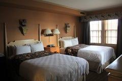 Gastslaapkamer met twee comfortabele bedden dichtbij venster, Sagamore Resort die, Bolton, New York, 2016 landen Stock Afbeelding